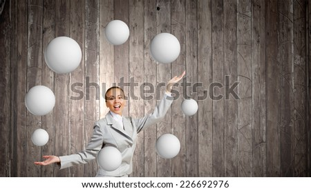 Young pretty businesswoman juggling with white balls - stock photo