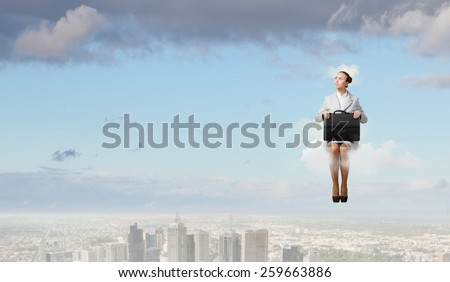 Young pretty businesswoman sitting on cloud high above city - stock photo