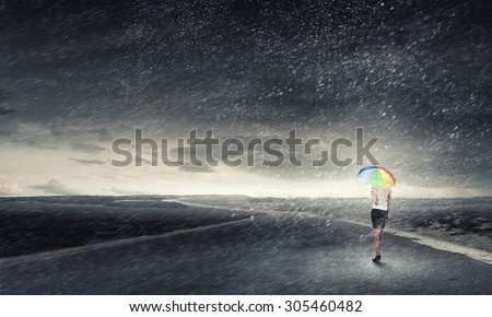 Young pretty businesswoman with rainbow colorful umbrella walking in storm - stock photo