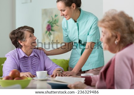Young pretty caring nurse and her two wards - stock photo