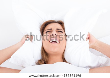 young pretty casual screaming woman in bed covering ears with pillow because of noise. Funny image. Noise or insomnia concept