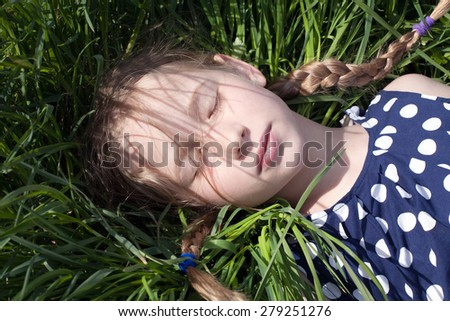 young pretty caucasian girl with two pigtail braids lying and sleeping on green grass - stock photo