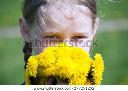 young pretty caucasian girl with yellow dandelions in hands, face closeup