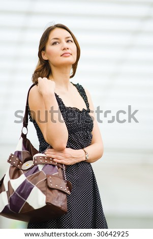 young pretty caucasian lady outdoor with handbag waiting for a friend - stock photo