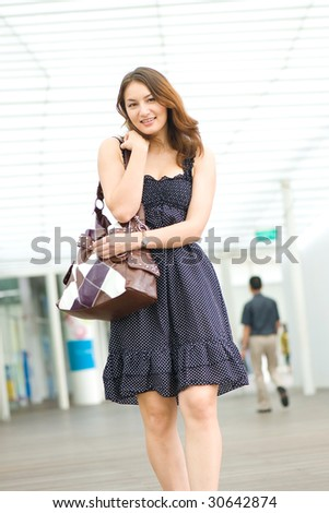 young pretty caucasian lady walking outdoor with handbag - stock photo