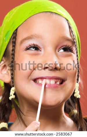 young pretty child applying make-up - stock photo