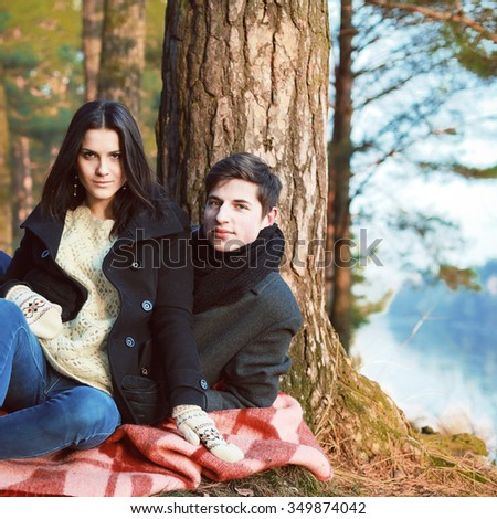 Young pretty couple in love having fun together outdoor in winter forest  - stock photo