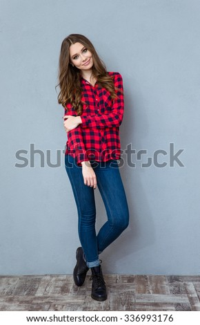 Young pretty curly woman in plaid shirt and jeans posing and smiling - stock photo