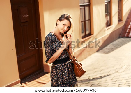 Young pretty cute student posing in city outdoor with cute smile and leather bag on shoulder.