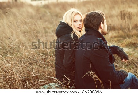 Young pretty fashion sensual couple in love sitting in winter cold field - stock photo
