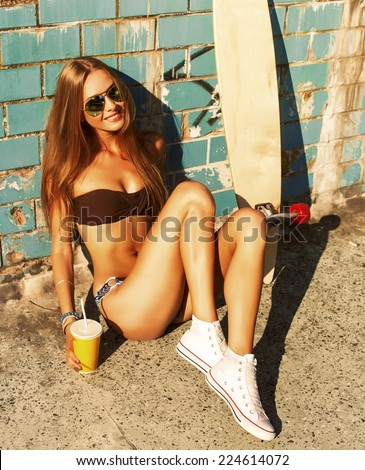 Young pretty fashion sexy blonde woman posing in summer in bikini with cocktail and longboard and have fun  - stock photo