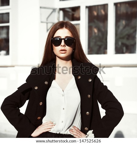 Young pretty fashion vogue brunette in sunglasses posing on the street in autumn - stock photo