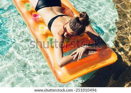 Young pretty fashion woman body posing in summer in pool with clear water lying on mattress in black bikini and having fun - stock photo