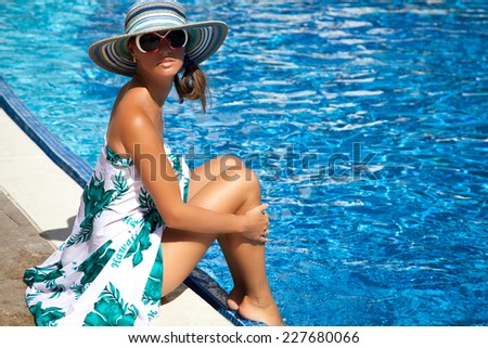 Young pretty fashion woman on summer holidays at swimming pool. Summer luxury vacation. - stock photo