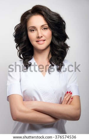 Young pretty female doctor in uniform keeping arms crossed, smiling and looking at camera while standing against grey background - stock photo