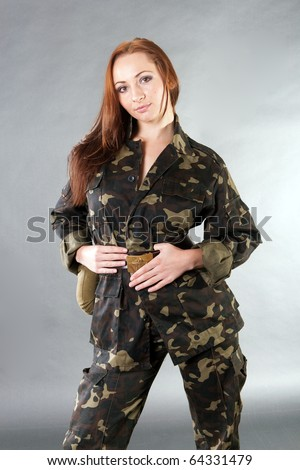 Young pretty female model in military outfit with water flask and USSR star belt in studio - stock photo