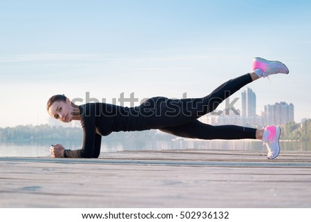 Young pretty fitness woman exercises on pier during morning sport training workout