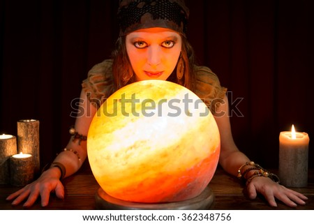 young pretty fortune teller with a shining crystal ball and candles, concept future and coaching - stock photo