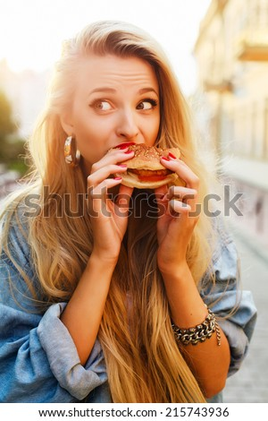Young pretty funny fashion sensual blond girl eats hamburger fast food sandwich on the street lifestyle outdoor photo  - stock photo