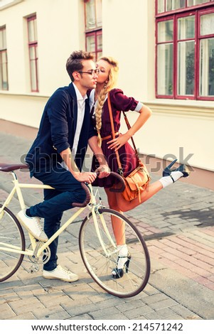 Young pretty funny hipster couple posing outdoor on the street with vintage bike. Girl gives lovely kiss to her boyfriend  - stock photo