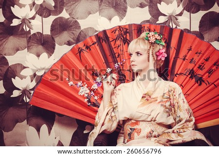 young pretty geisha in kimono with flower and decoration - stock photo