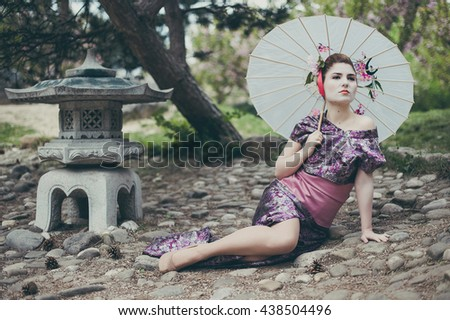 young pretty geisha  wearing traditional japanese kimono and traditional umbrella - stock photo