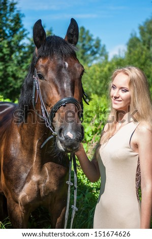 Young pretty girl and a horse in the forest - stock photo