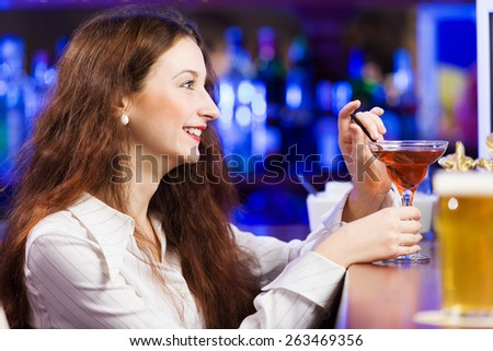 Young pretty girl at bar drinking cocktail