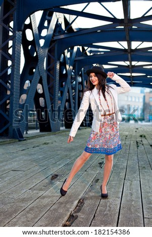 Young pretty girl elegantly dressed posing on old iron bridge. Cute Caucasian model.