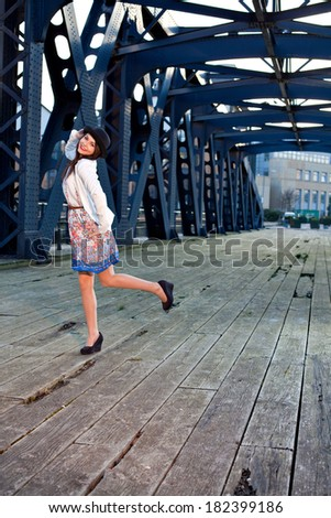 Young pretty girl elegantly dressed posing on old iron bridge. Cute Caucasian model. - stock photo