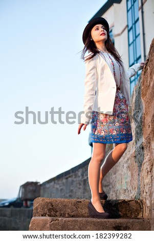 Young pretty girl elegantly dressed posing on old stone stairs. Cute Caucasian model. - stock photo