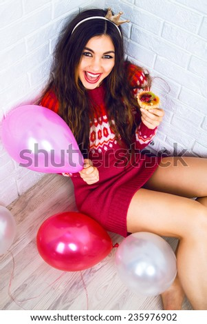 Young pretty girl having fun on birthday party, wearing party crown casual sweater, holding pink balloon and tasty small cake. Positive emotions, read for celebration. - stock photo