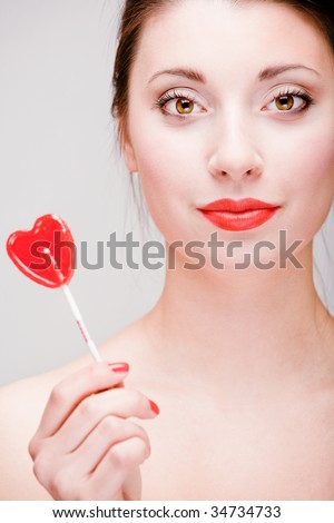 Young pretty girl holding a lollipop