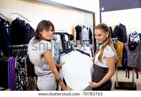 young pretty girl in a shop buying clothes - stock photo