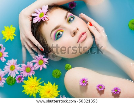 Young pretty girl in blue water - stock photo