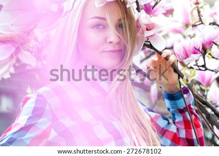 Young pretty girl in pink flowers enjoying life. Outdoors at spring - stock photo