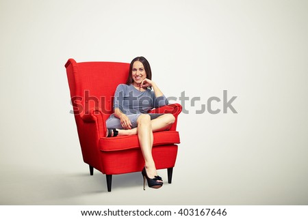 Young pretty girl is smiling and holding her hand near chin while sitting in soft red chair  - stock photo