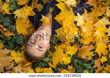 Young pretty girl lying in autumn leaves. - stock photo