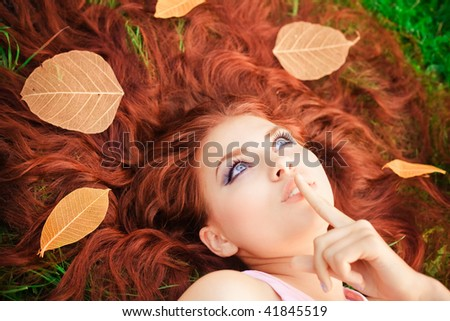 Young pretty girl lying on grass - stock photo