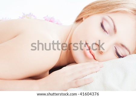 Young pretty girl lying with closed eyes - stock photo