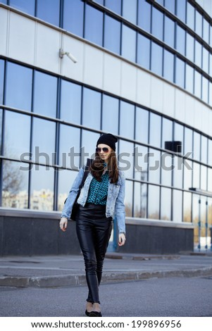 young pretty girl near business building walking - stock photo