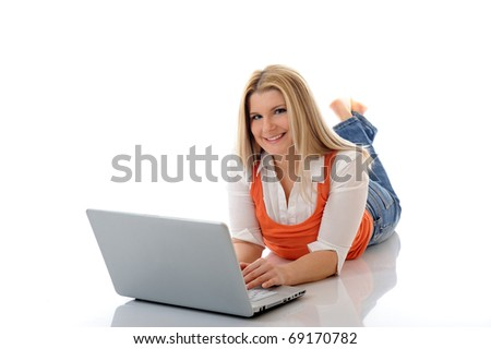 Young pretty girl networking on laptop computer in internet. isolated on white background - stock photo