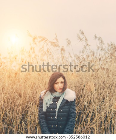 Young pretty girl on the lake in autumn sunny day - stock photo
