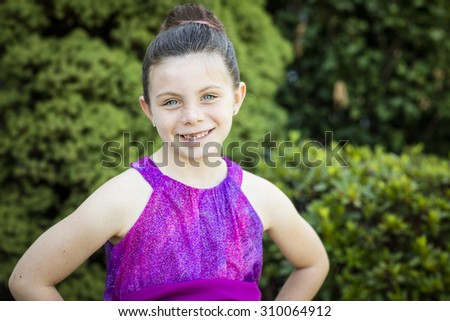 Young pretty girl poses outside against green background - stock photo