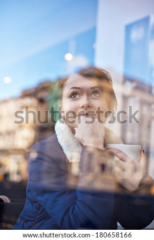Young pretty girl sitting inside a modern cafe drinking coffee or tea. Cute Caucasian model. View from outside - stock photo