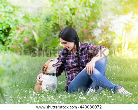 Young pretty girl sitting on grass in the park with her dog - stock photo
