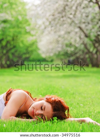 Young pretty girl sleeping in grass - stock photo