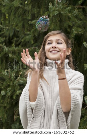 Young pretty girl throwing and catching a pine cone near a fire tree outside - stock photo