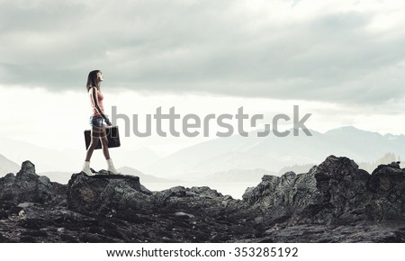 Young pretty girl walking with her retro suitcase in hand