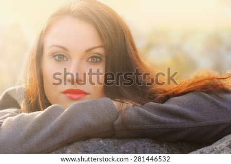 Young pretty girl warming up on cold autumnal weather - stock photo